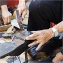Small photo of elderly man repairing a shoe
